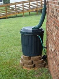 Rain barrel attached to a gutter system of a house